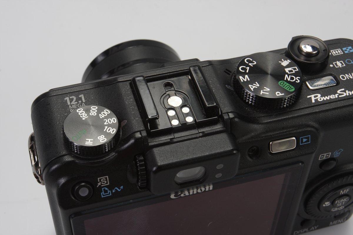 De knop voor het instellen van de gevoeligheid zit bij deze compactcamera helemaal links.